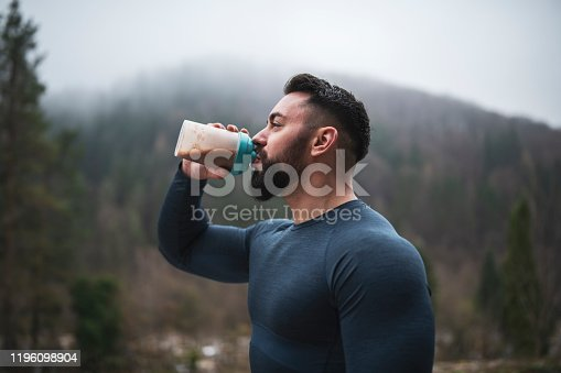 Sportsman drinking protein in shaker bottle outdoor in front of foggy hill in autumn season, close up, drinking water after outdoor exercise.