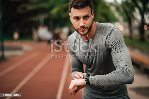 istock Sportsman. Exercising. Fitness lover. Body Building. Man doing exercise in park 1155494356