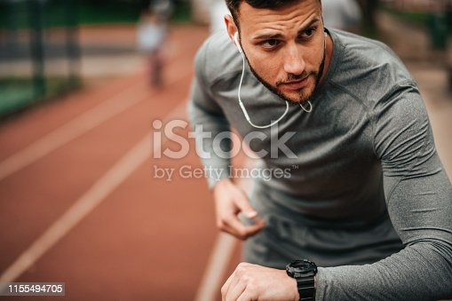 istock Sportsman. Exercising. Fitness lover. Body Building. Man doing exercise in park 1155494705