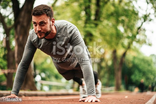 istock Sportsman. Exercising. Fitness lover. Body Building. Man doing exercise in park 1155498376