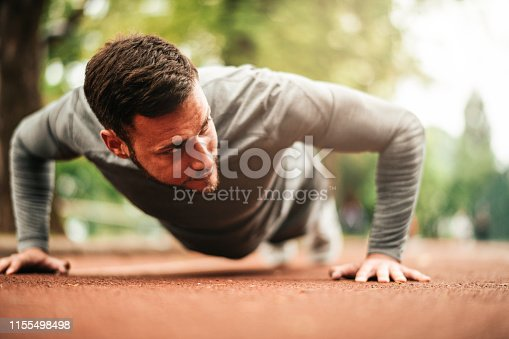 istock Sportsman. Exercising. Fitness lover. Body Building. Man doing exercise in park 1155498498