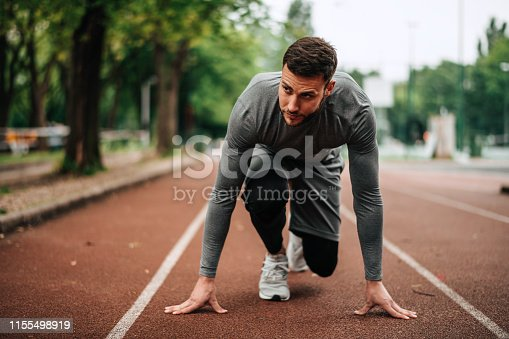 istock Sportsman. Exercising. Fitness lover. Body Building. Man doing exercise in park 1155498919