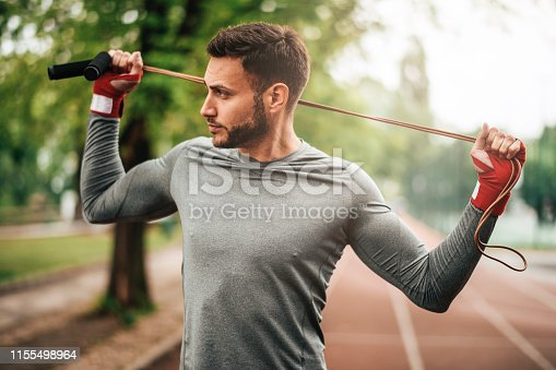 istock Sportsman. Exercising. Fitness lover. Body Building. Man doing exercise in park 1155498964