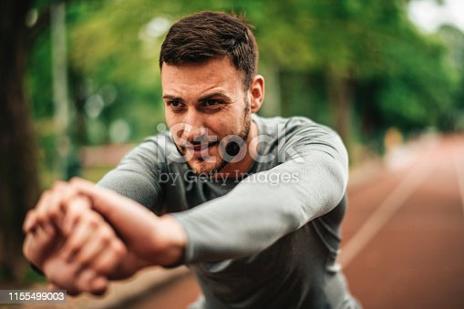 istock Sportsman. Exercising. Fitness lover. Body Building. Man doing exercise in park 1155499003