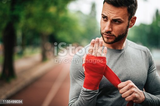 istock Sportsman. Exercising. Fitness lover. Body Building. Man doing exercise in park 1155499034