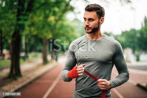 istock Sportsman. Exercising. Fitness lover. Body Building. Man doing exercise in park 1155499190