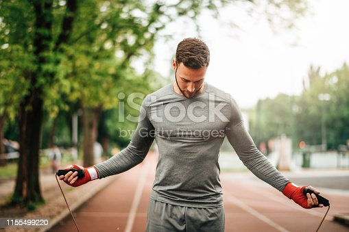 istock Sportsman. Exercising. Fitness lover. Body Building. Man doing exercise in park 1155499220