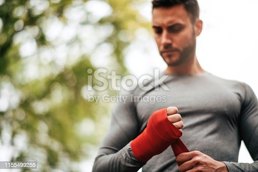istock Sportsman. Exercising. Fitness lover. Body Building. Man doing exercise in park 1155499255