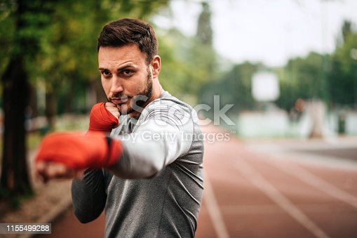 istock Sportsman. Exercising. Fitness lover. Body Building. Man doing exercise in park 1155499288