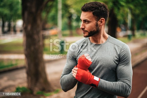 istock Sportsman. Exercising. Fitness lover. Body Building. Man doing exercise in park 1155499324