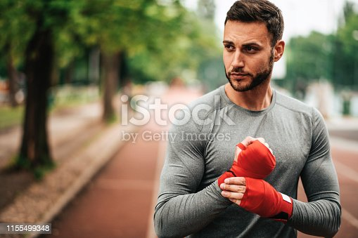 istock Sportsman. Exercising. Fitness lover. Body Building. Man doing exercise in park 1155499348