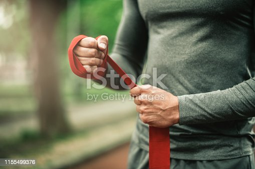 istock Sportsman. Exercising. Fitness lover. Body Building. Man doing exercise in park 1155499376