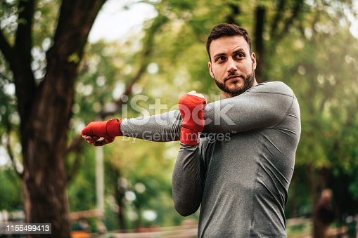 istock Sportsman. Exercising. Fitness lover. Body Building. Man doing exercise in park 1155499413