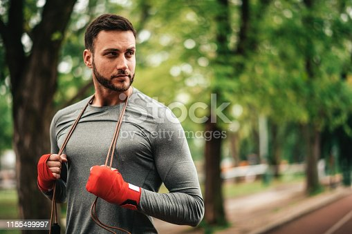 istock Sportsman. Exercising. Fitness lover. Body Building. Man doing exercise in park 1155499997