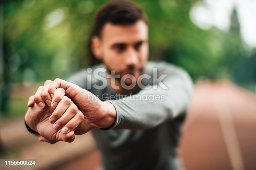 istock Sportsman. Exercising. Fitness lover. Body Building. Man doing exercise in park 1155500524
