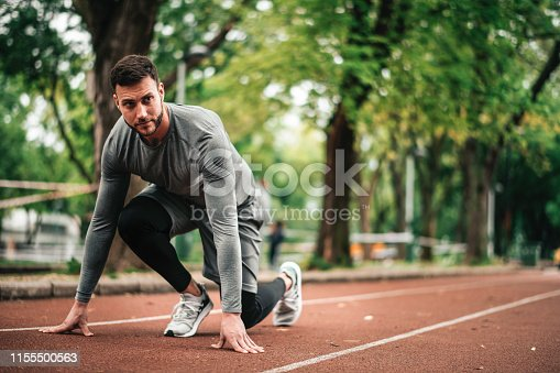 istock Sportsman. Exercising. Fitness lover. Body Building. Man doing exercise in park 1155500563