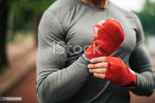 istock Sportsman. Exercising. Fitness lover. Body Building. Man doing exercise in park 1155500595