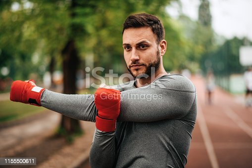 istock Sportsman. Exercising. Fitness lover. Body Building. Man doing exercise in park 1155500611