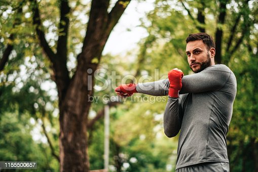 istock Sportsman. Exercising. Fitness lover. Body Building. Man doing exercise in park 1155500657