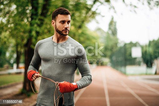 istock Sportsman. Exercising. Fitness lover. Body Building. Man doing exercise in park 1155500746