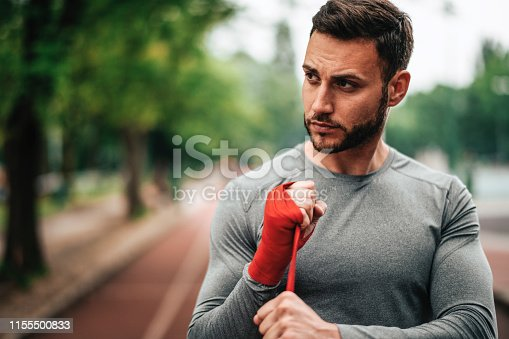 istock Sportsman. Exercising. Fitness lover. Body Building. Man doing exercise in park 1155500833