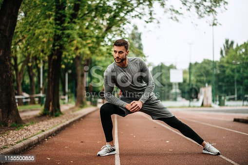 istock Sportsman. Exercising. Fitness lover. Body Building. Man doing exercise in park 1155500855