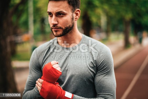 istock Sportsman. Exercising. Fitness lover. Body Building. Man doing exercise in park 1155500906