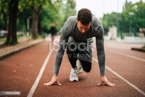 istock Sportsman. Exercising. Fitness lover. Body Building. Man doing exercise in park 1155500986
