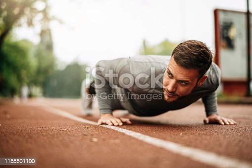istock Sportsman. Exercising. Fitness lover. Body Building. Man doing exercise in park 1155501100