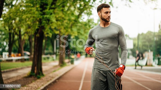 istock Sportsman. Exercising. Fitness lover. Body Building. Man doing exercise in park 1155501132
