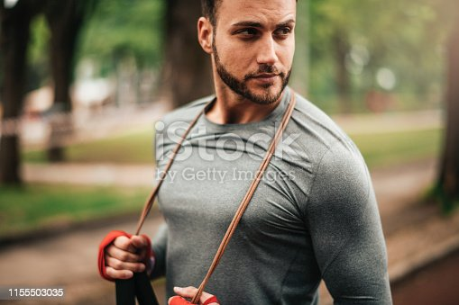 istock Sportsman. Exercising. Fitness lover. Body Building. Man doing exercise in park 1155503035