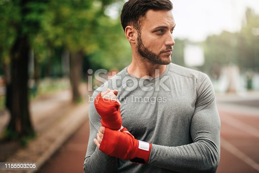 istock Sportsman. Exercising. Fitness lover. Body Building. Man doing exercise in park 1155503205