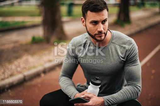 istock Sportsman. Exercising. Fitness lover. Body Building. Man doing exercise in park 1155503370