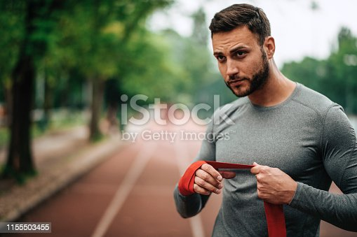 istock Sportsman. Exercising. Fitness lover. Body Building. Man doing exercise in park 1155503455