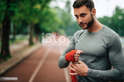 istock Sportsman. Exercising. Fitness lover. Body Building. Man doing exercise in park 1155503608