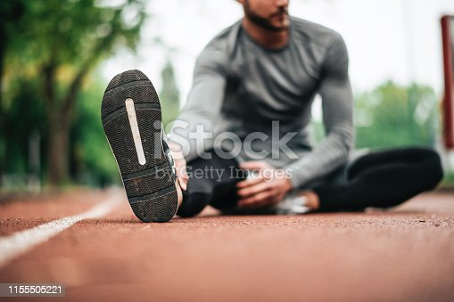 istock Sportsman. Exercising. Fitness lover. Body Building. Man doing exercise in park 1155505221