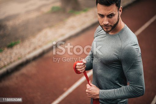 istock Sportsman. Exercising. Fitness lover. Body Building. Man doing exercise in park 1155505388