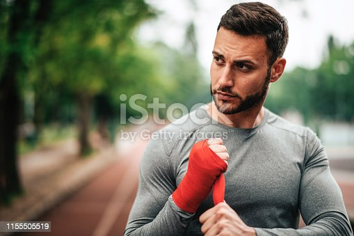 istock Sportsman. Exercising. Fitness lover. Body Building. Man doing exercise in park 1155505519