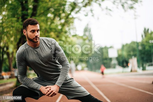 istock Sportsman. Exercising. Fitness lover. Body Building. Man doing exercise in park 1155506088
