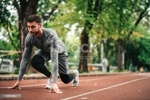 istock Sportsman. Exercising. Fitness lover. Body Building. Man doing exercise in park 1155506277