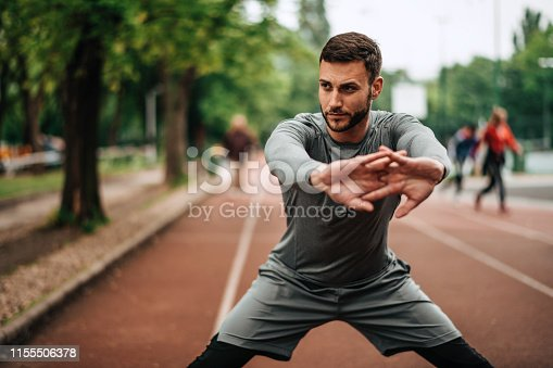 istock Sportsman. Exercising. Fitness lover. Body Building. Man doing exercise in park 1155506378