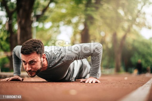 istock Sportsman. Exercising. Fitness lover. Body Building. Man doing exercise in park 1155506743