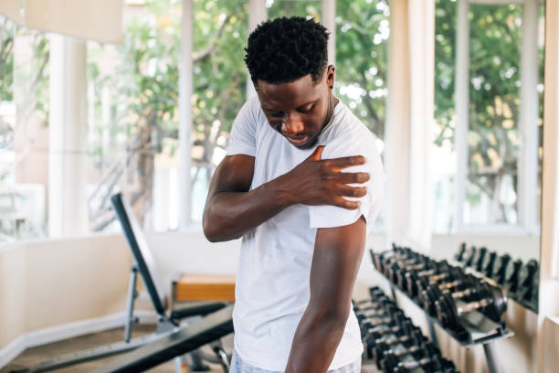 Sportsman holding painful shoulder in gym stock photo