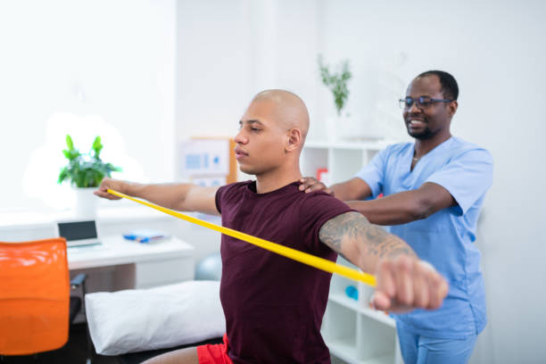 sportsman holding ribbon stretching arms visiting therapist - medicina sportiva foto e immagini stock