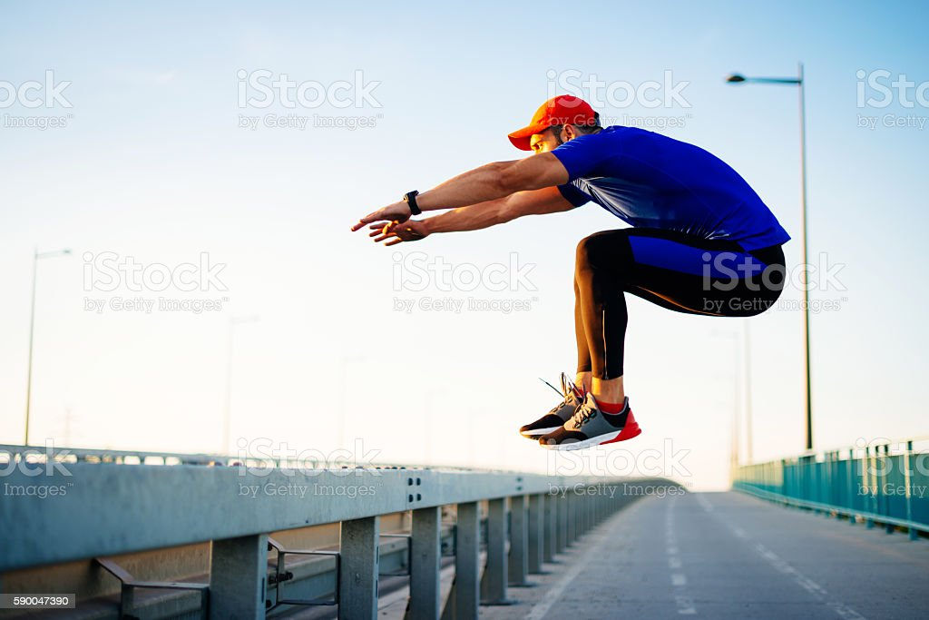 Sportsman jumping over barriers during parkour training stock photo