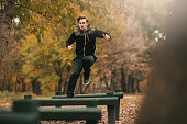 An attractive young sportsman is seen in the park jumping over obstacles.