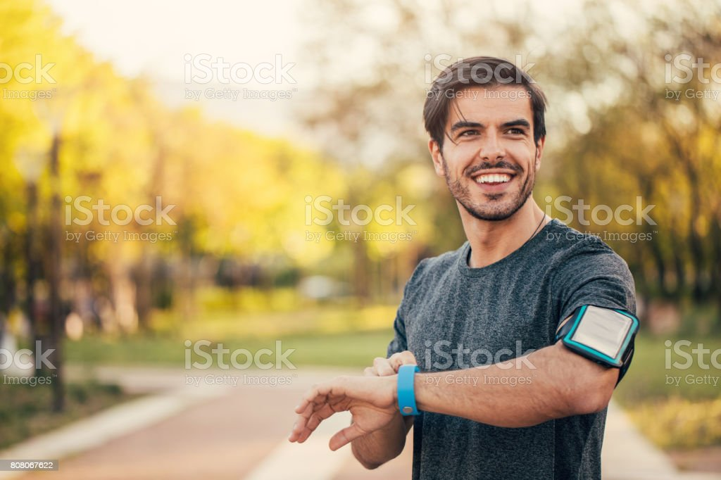 Sportsman looking at his smart watch