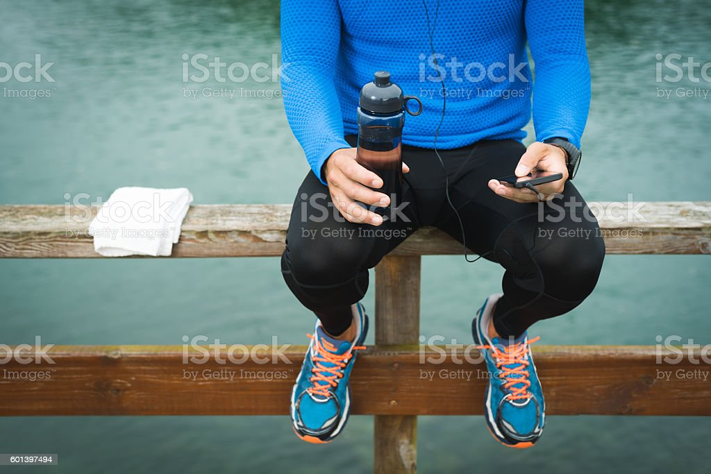 Sportsman looking to the phone for motivation before workout outdoors – Foto