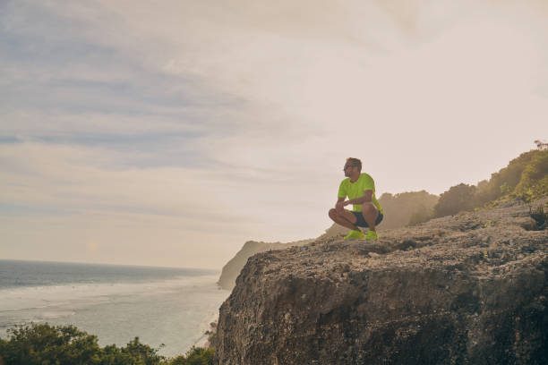 Sportsman making pause after workout on a tropical cliff. stock photo