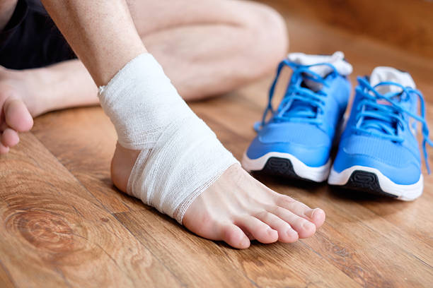sportsman massaging his injured ankle after a sport accident stock photo